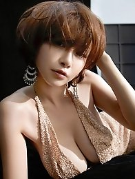Anri Sugihara posing her super big breasts in a satin dress