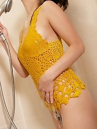 Busty and cute Japanese av idol Megumi Haruka wears a yellow one piece and takes shower